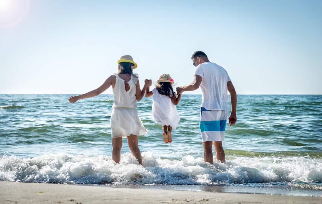Happy family enjoying the waves at the beach